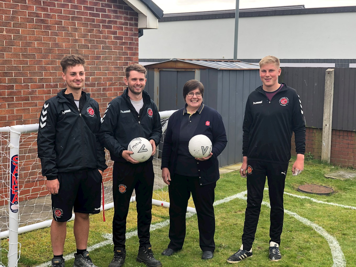 Salvation Army Chaplain Major Maggie Cadogan with Fleetwood Town grounds staff Liam Scott-Rattray, Nick Hyndman, and Max Knapman on the new pitch.jpg